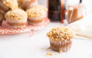 A single Spiced Pumpkin Muffin is on a white surface. A french press of coffe and a glass jar of spice in right background.