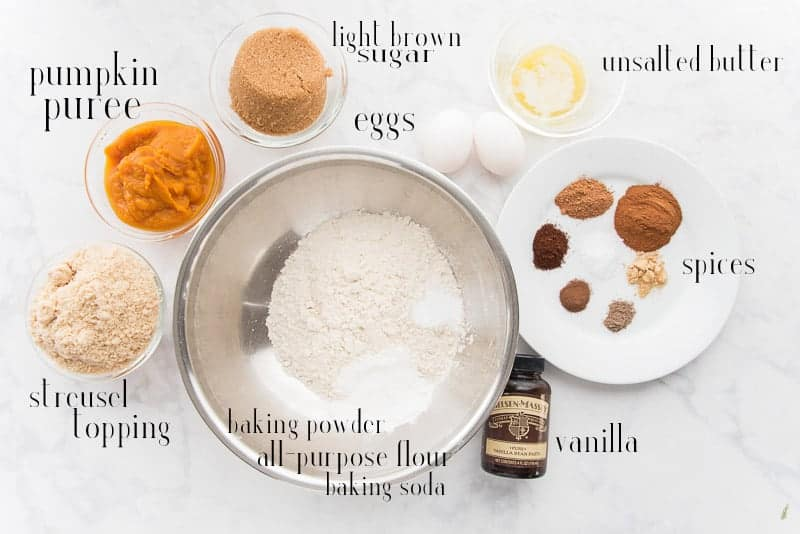 the ingredients needed to make spiced pumpkin muffins on a white surface
