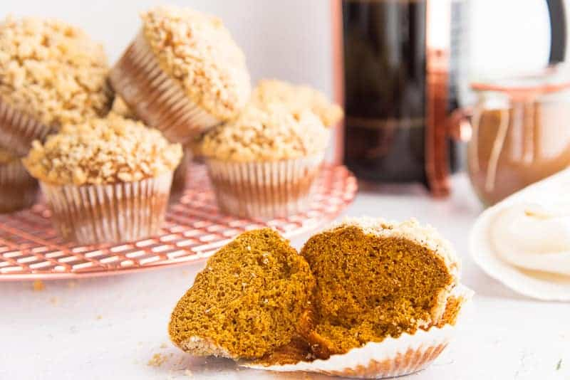 a Spiced Pumpkin Muffin is broken in half revealing the interior.