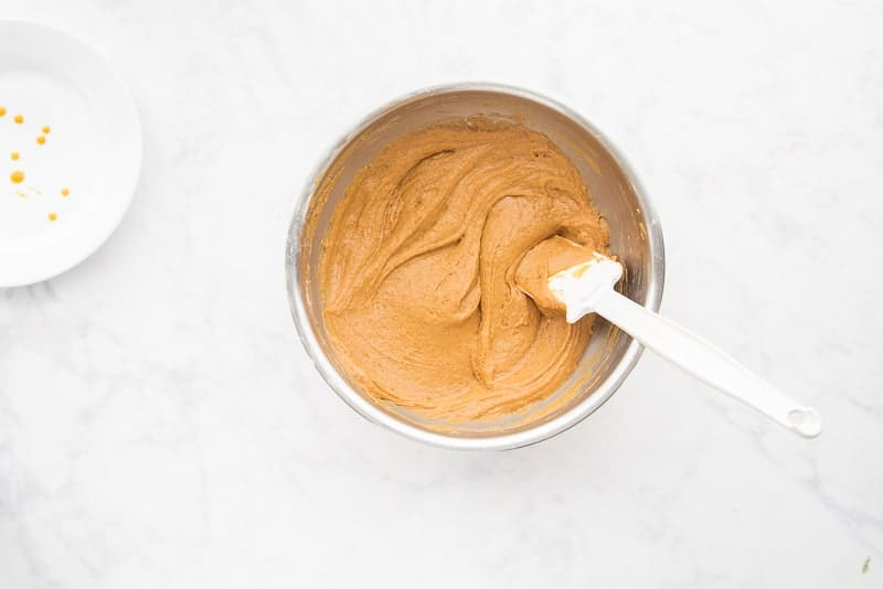 The spiced pumpkin muffin batter is blended in a silver mixing bowl a white spatula is in the bowl.