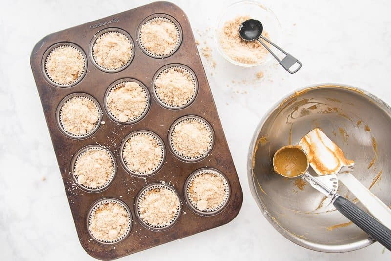 the muffin batter is scooped into a dark metal muffin pan and topped with streusel