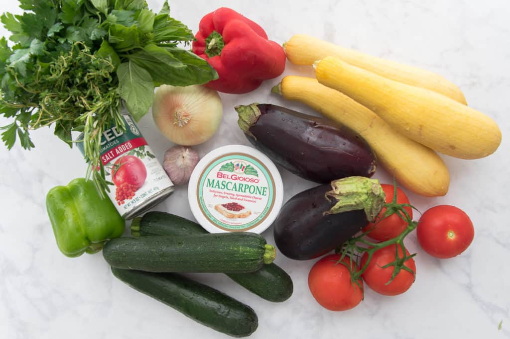 Ingredients used to make Italian Ratatouille are shown: mixed herbs, onion, garlic, red pepper, yellow squash, eggplant, tomatoes, mascarpone cheese, zucchini, a can of diced tomatoes, a green bell pepper
