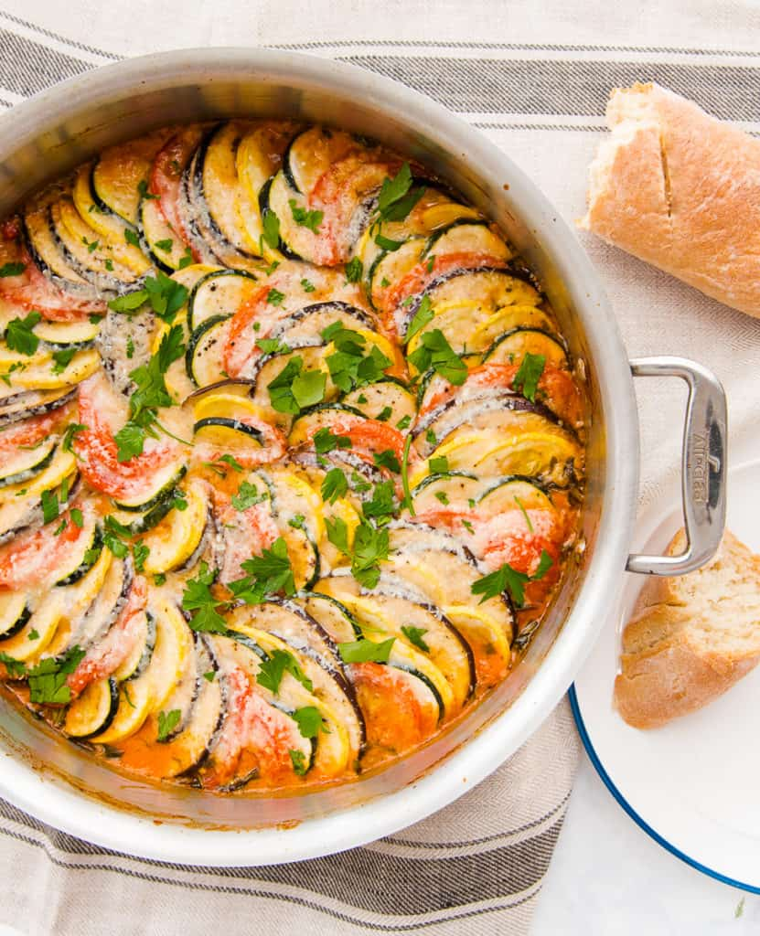 An overhead view of a pan filled with the baked Italian Ratatouille. A piece of bread sits on a white plate to the bottom right. A broken loaf of bread peeks out from the top right hand side of the image.