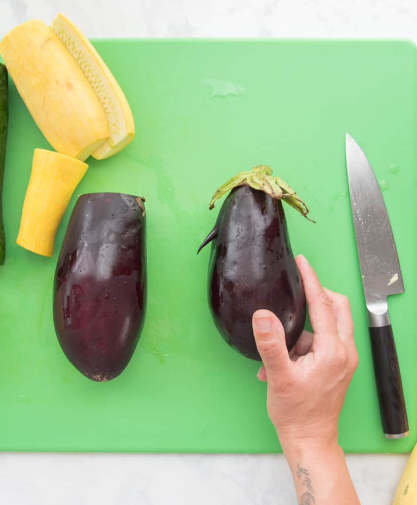 A misshapen eggplant is held up to see against a green cutting board. A knife sits at the right hand side.