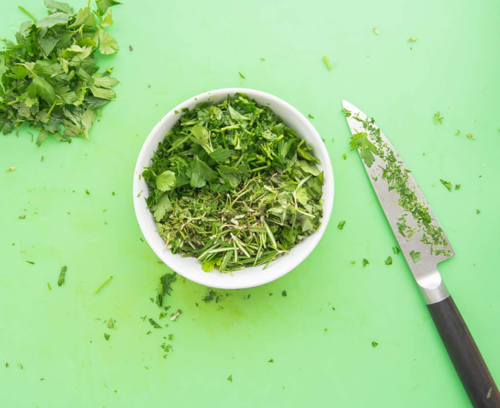 A white bowl filled with green herbs sits on a green cutting board. The knife that was used to chop the herbs sits to the right of the bowl