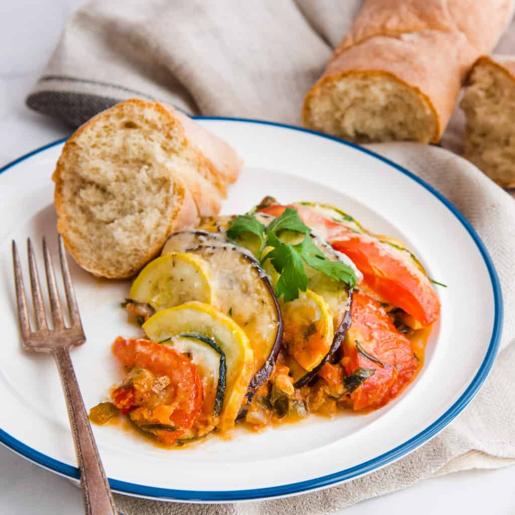 A close-up, horizontal image of Italian Ratatouille on a blue-rimmed white plate. A piece of bread sits at 10 o'clock on the plate. Two halves of a bread loaf are in the background