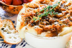 A side view of a gooey Baked Brie with Caramelized Onion