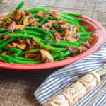 A red plate with Haricot Verts with Bacon and Portobellos