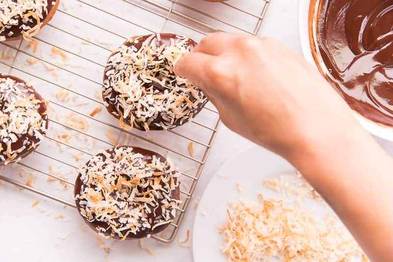 A hand sprinkles toasted coconut flakes over a chocolate covered cake donut