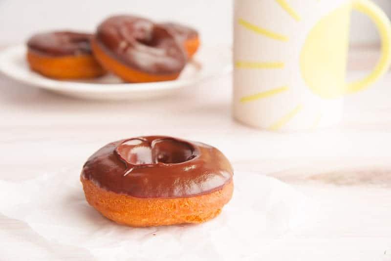A chocolate ganache cake donut in front of a sunshine coffee mug