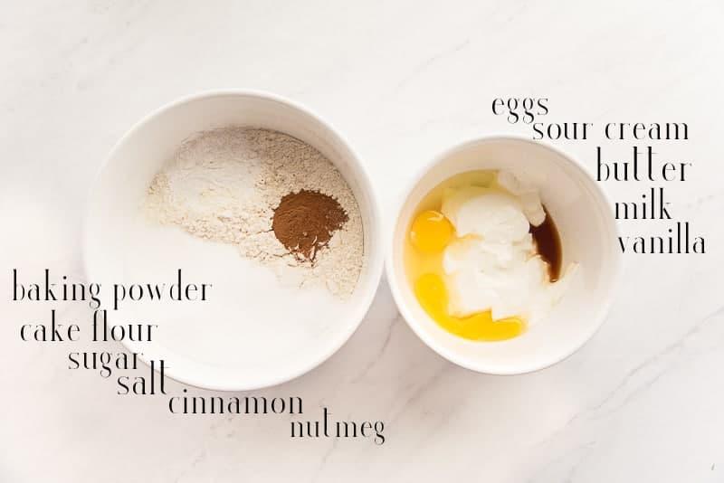 Ingredients to make Easy Cake Donuts: baking powder, cake flour, salt, cinnamon, nutmeg, butter, sour cream, vanilla, eggs, milk and sugar in two white bowls