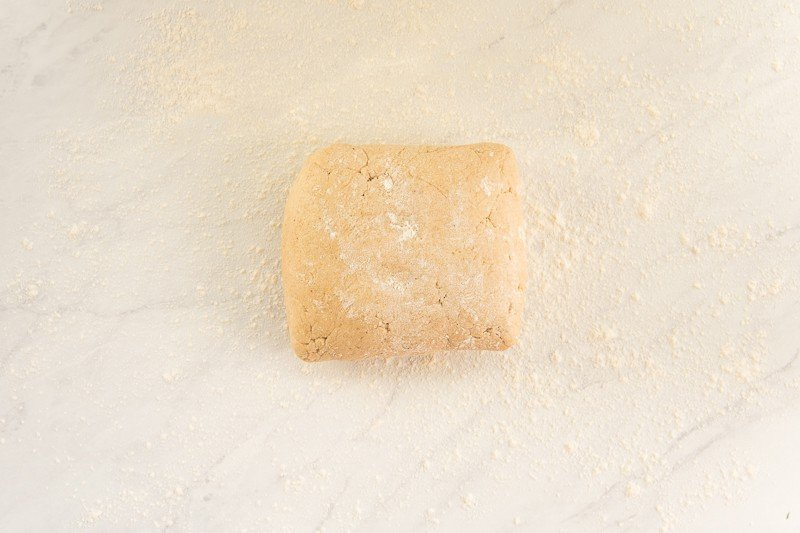 The square of cake donuts dough on a floured surface