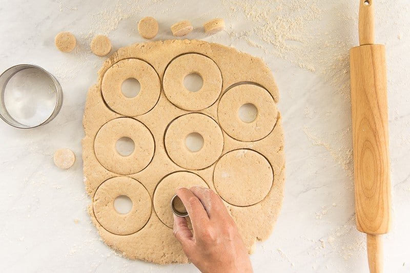 A hand uses a small circle cutter to cut a center out of a donut