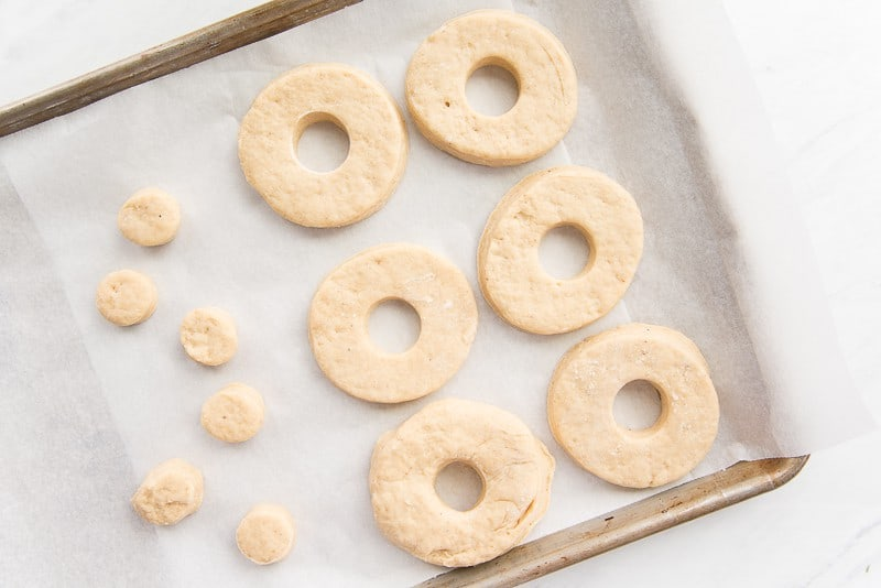 Raw cake donuts on a sheetpan for baking.
