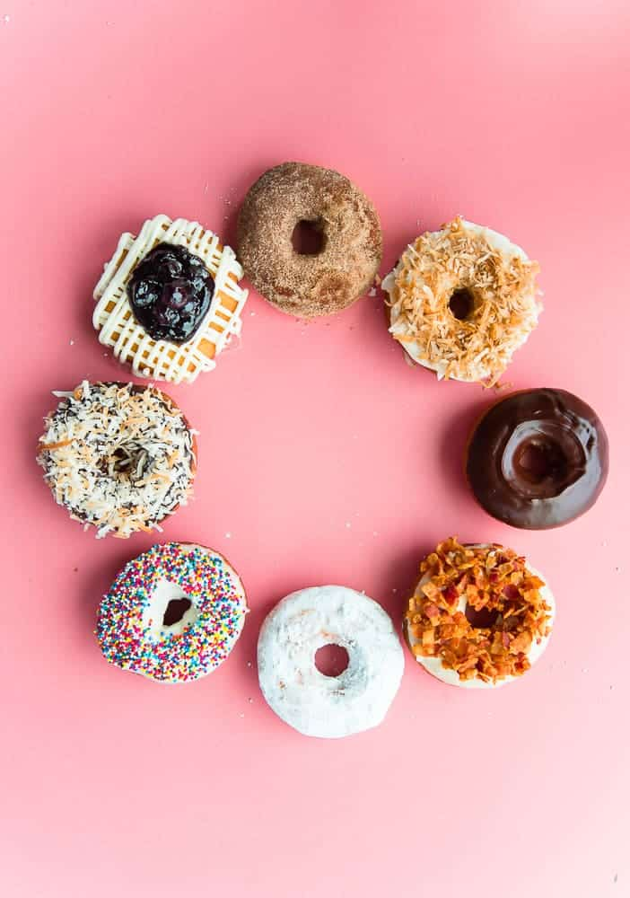 Easy cake donuts recipe lead image of a circle of donuts on a coral background