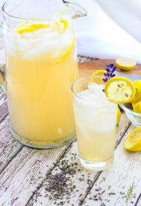 A glass of lemonade with a pitcher in background