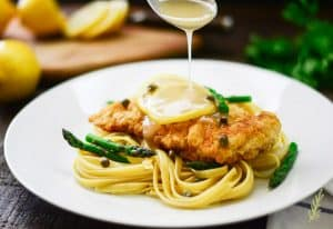 A ladle drizzles sauce over the Chicken Piccata with Asparagus