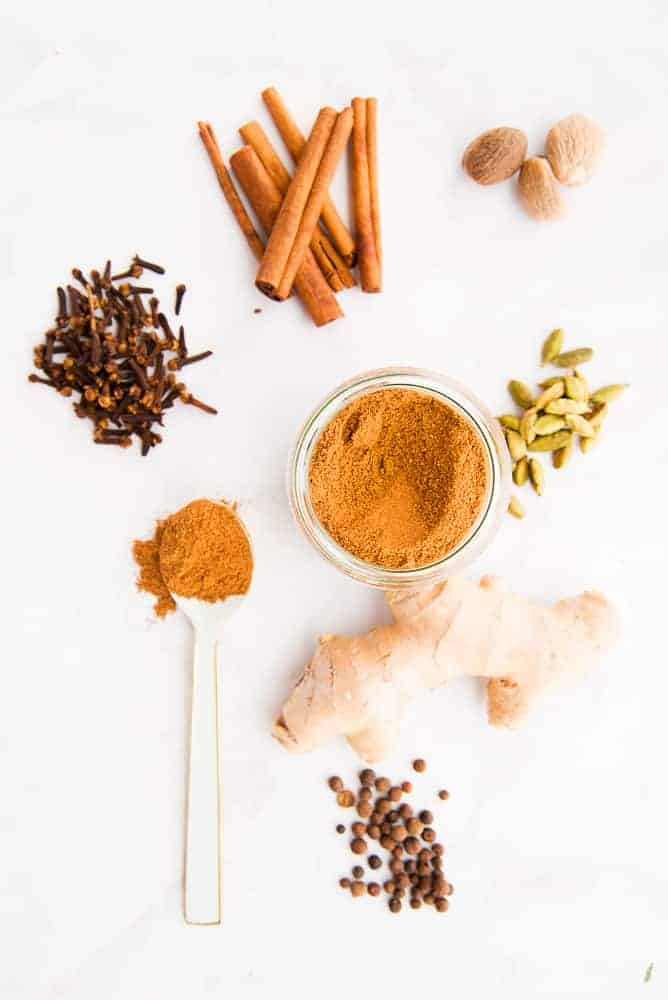 Pumpkin Pie Spice Blend in a glass jar surrounded by whole spices.