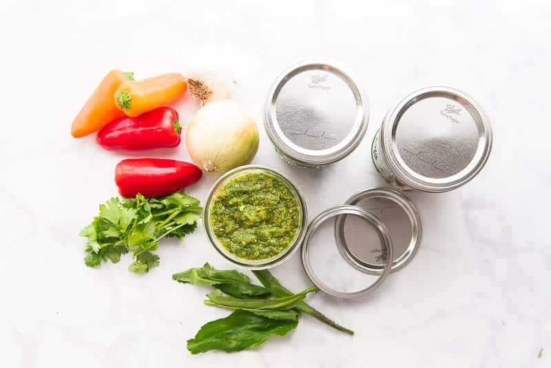 An overhead image of three jars of sofrito (top are capped).