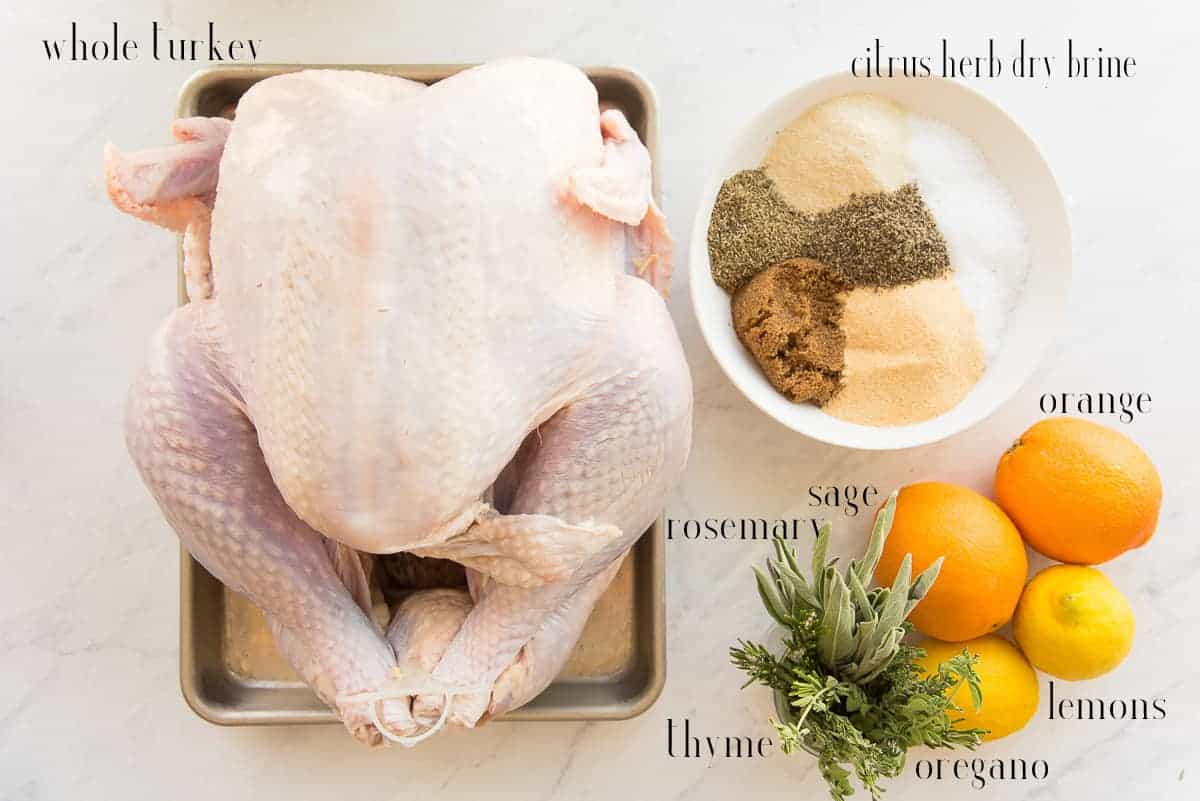 Ingredients needed to dry brine and roast a turkey: turkey, citrus herb dry brine, orange, lemons, sage, thyme, rosemary, and oregano.