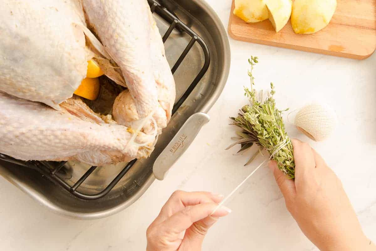 Hands tie a herb bundle together with twine before inserting it into the cavity of a turkey