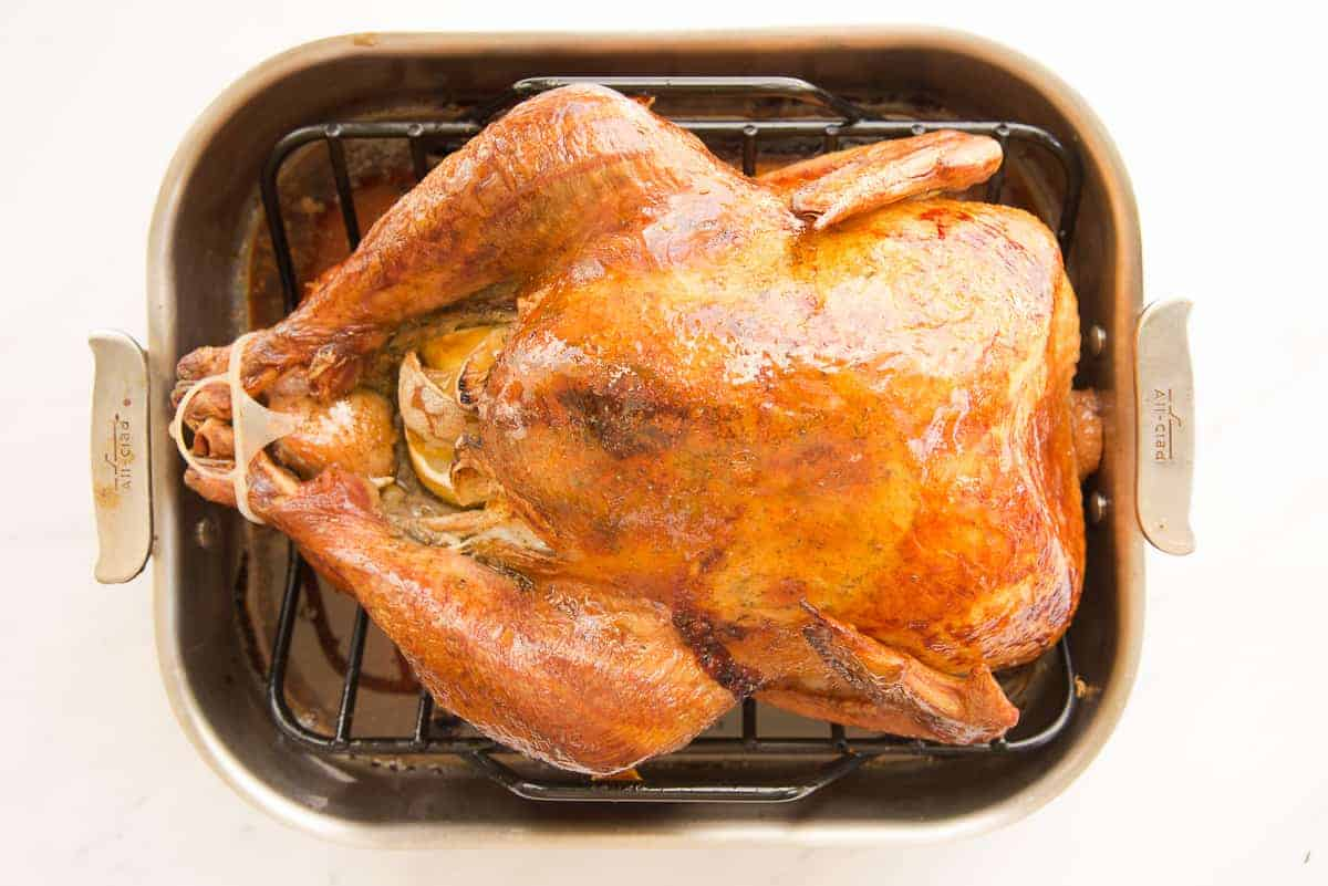 The dry brine and roast turkey is golden brown in its roasting pan.