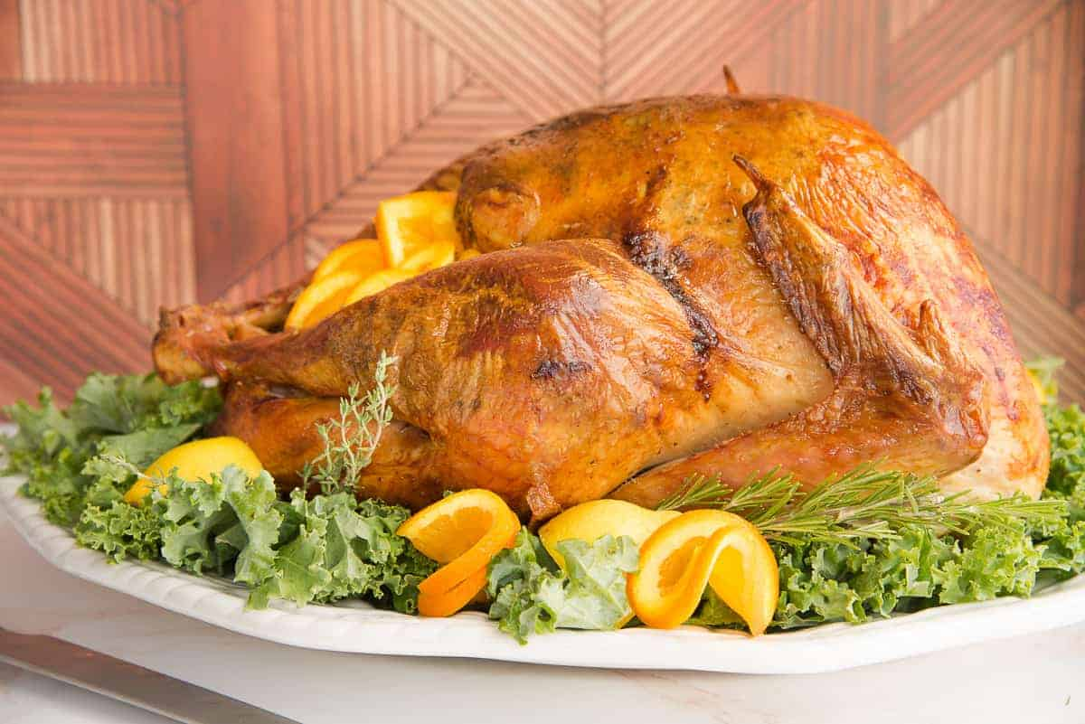 dry brine roast turkey on a bed of greens surrounded by furled orange and lemon slices.