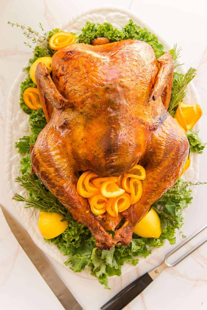 Portrait image of a dry brine roast turkey on a white platter with a bed of greens, lemon wedges, and furled orange slices