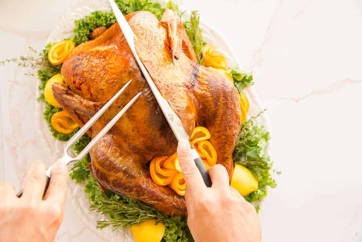 hand use a carving knife and fork to slice breast meat from a dry brine roast turkey.