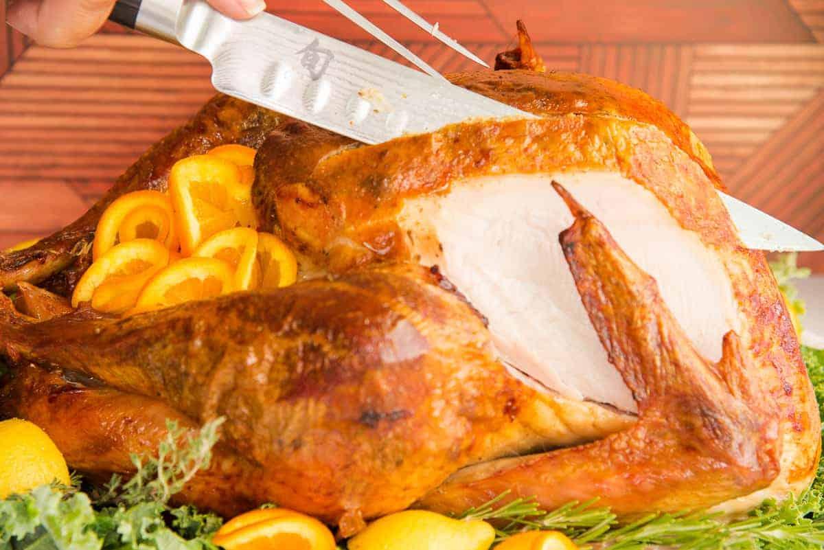 Knife carves the dry brine roast turkey breast (sideview).