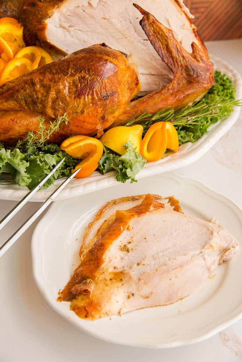 Portrait image of a slice of dry brine roast turkey on a white plate next to the platter of turkey.