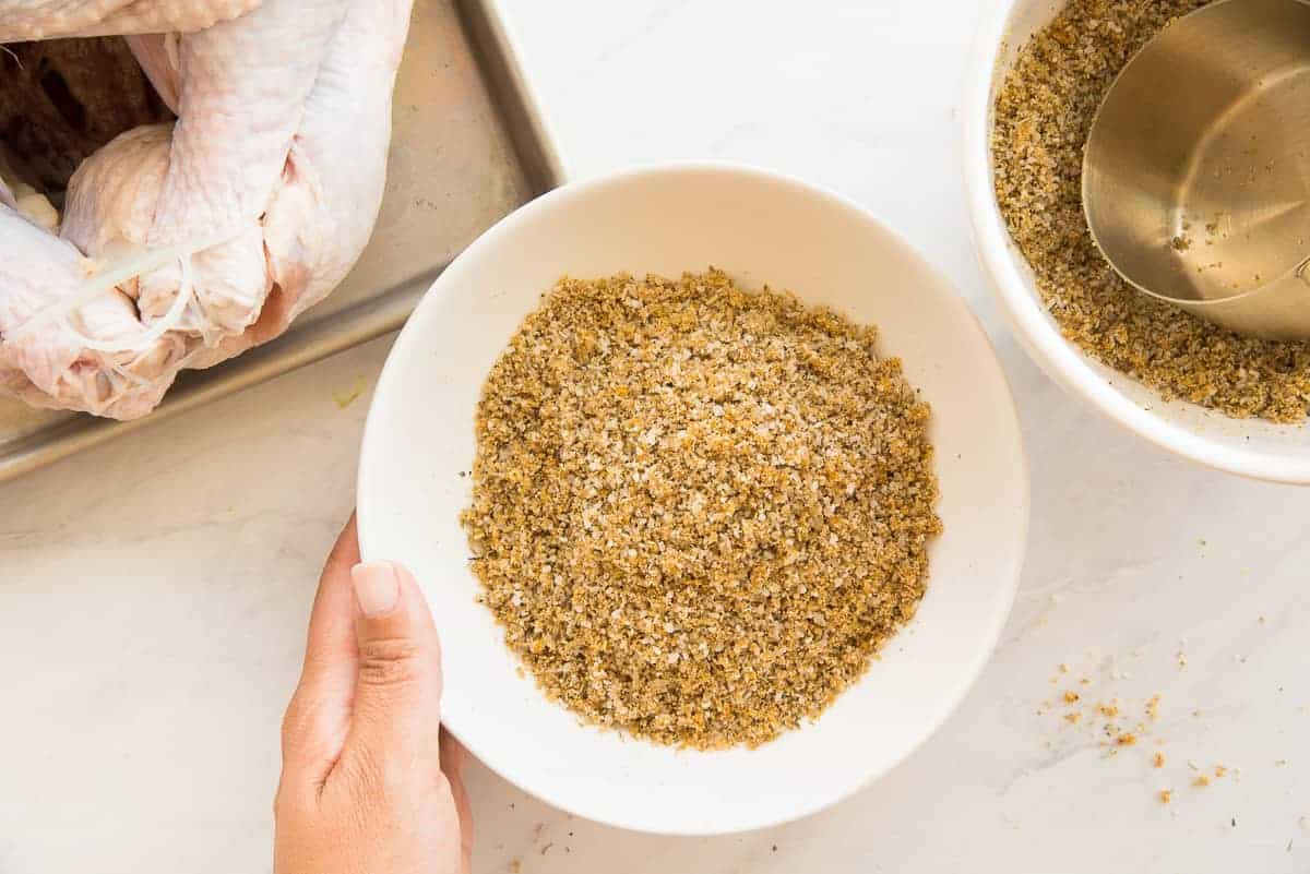 Hand touching a white bowl filled with citrus herb spice blend.