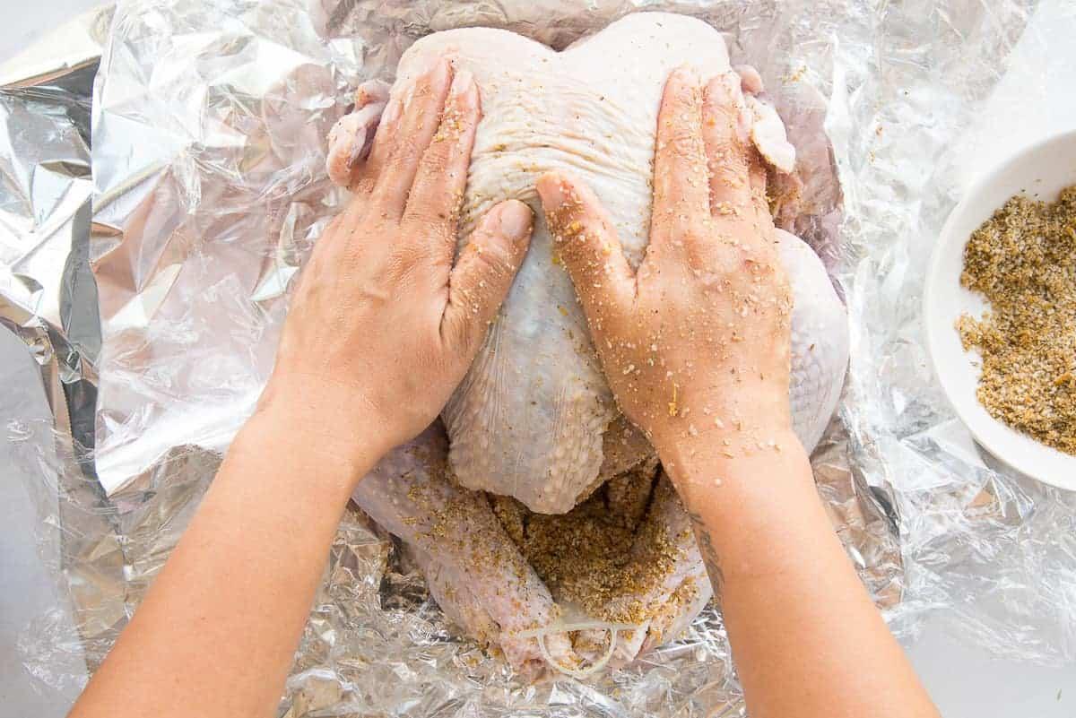 Dry brine is massaged into the turkey skin.