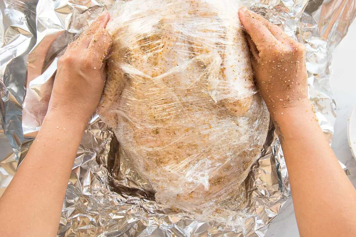 Hands wrap the dry brine turkey in plastic wrap before wrapping in foil.