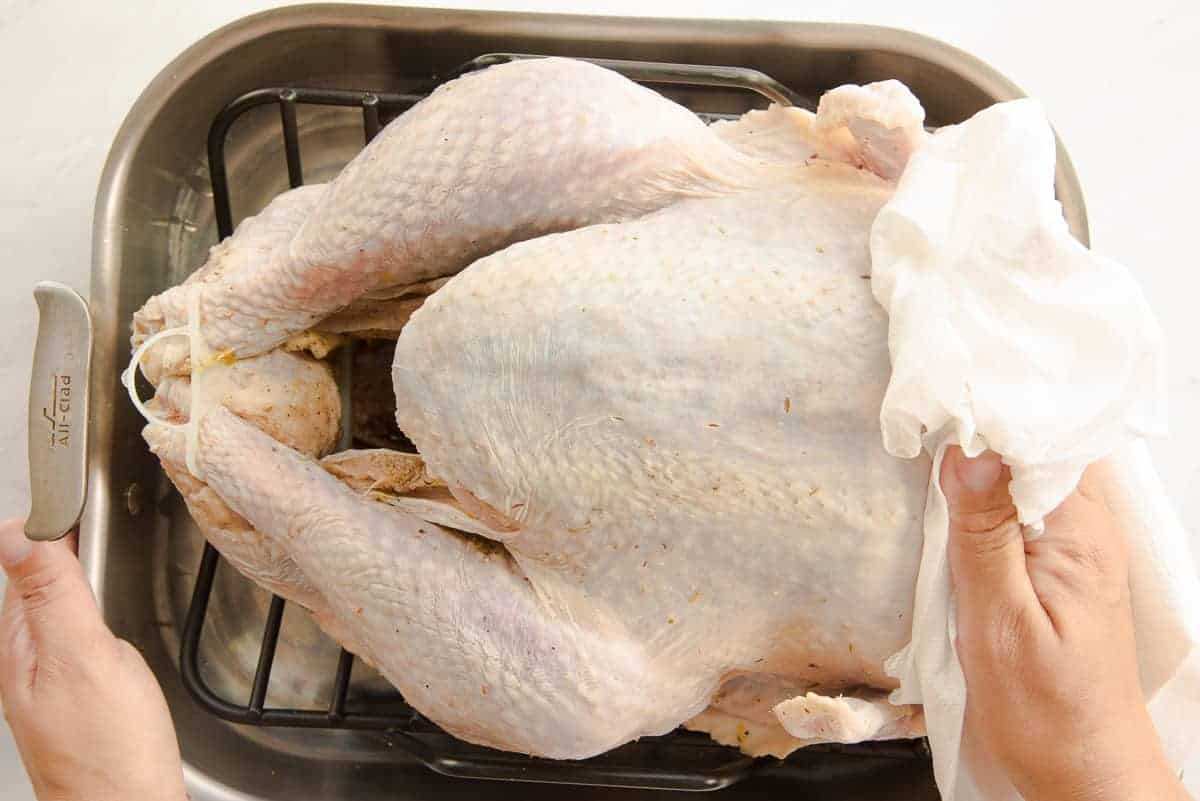 A hand dries the surface of the turkey with a paper towel