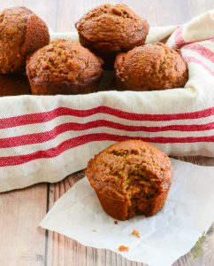 A batch of Persimmon-Walnut Muffins in a basket with a red-striped kitchen towel. A muffin with a bite taken out of it sits in front on a white square of paper.