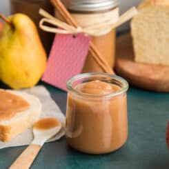 Preview for Slow Cooker Apple Pear Butter. Small glass jar of the fruit spread next to a slice of bread with the spread on it.