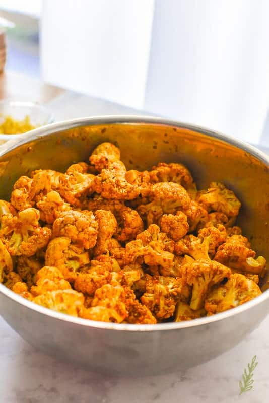 The cauliflower is coated in the curry sauce in a large silver bowl.