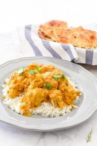 A serving of Vegetarian Curried Cauliflower on a bed of rice on a grey plate