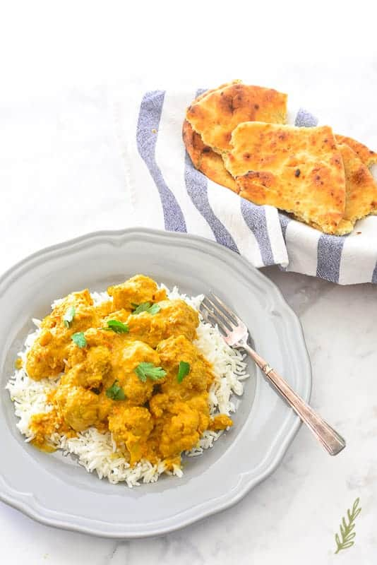 Vegetarian Curried Cauliflower on a bed of white rice on a grey plate. A serving of naan is in the right background.
