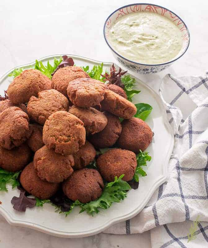 A plate of Egyptian Falafel sits on a checked blue and white towel next to a bowl of tahini sauce