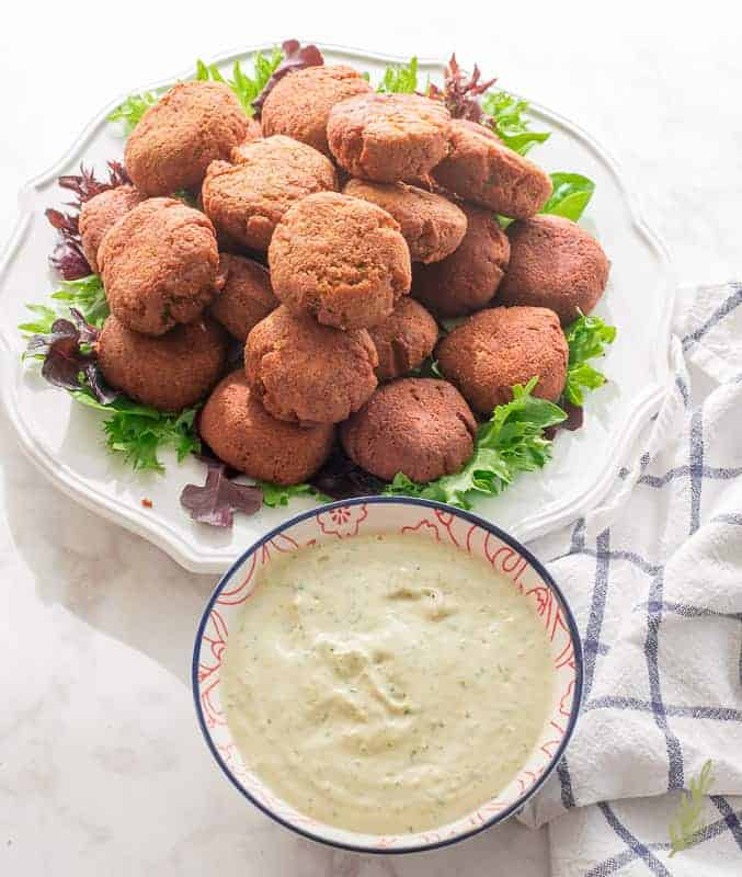 A plate is piled high with Egyptian Falafel. In front of the plate is a bowl of tahini sauce.