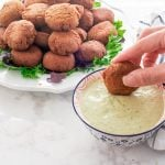 A hand dips an Egyptian Falafel into a bowl of tahini sauce