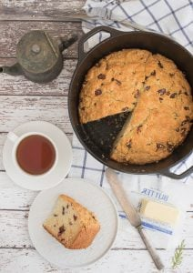 A slice of Irish Soda Bread next to the baked loaf and a cup of tea