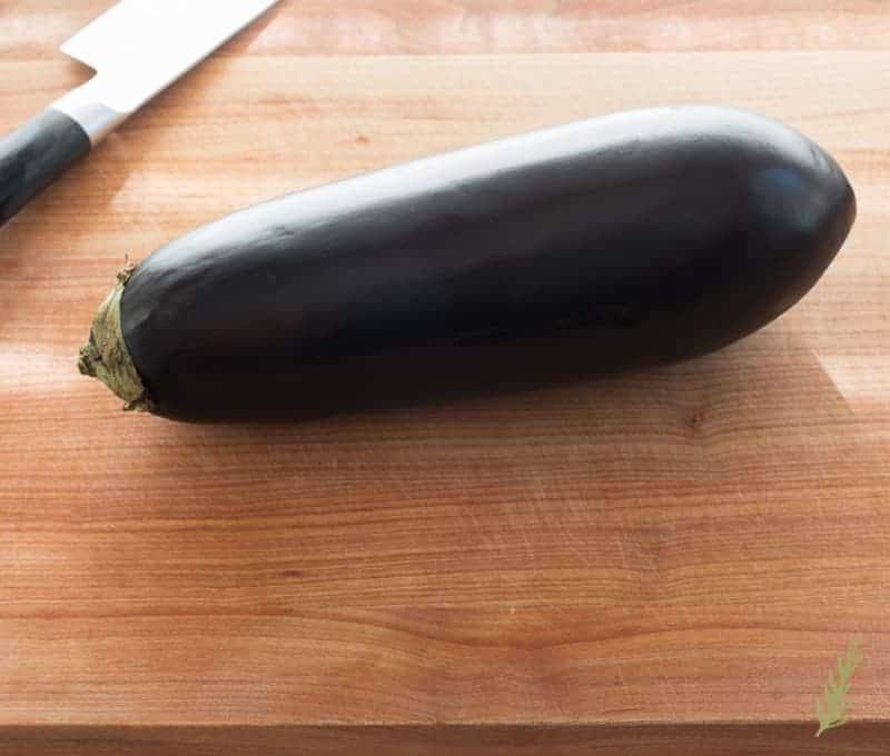 A purple eggplant on a wooden cutting board
