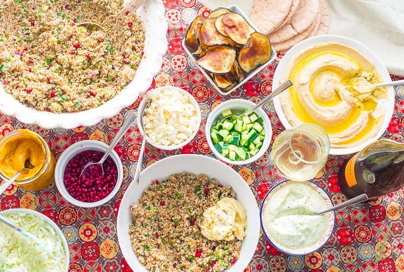 A dollop of hummus is added to the tabbouleh in a white bowl for the Sabich bowls