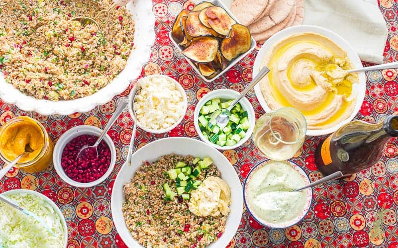 Cucumber is added to the bowl of tabbouleh and hummus