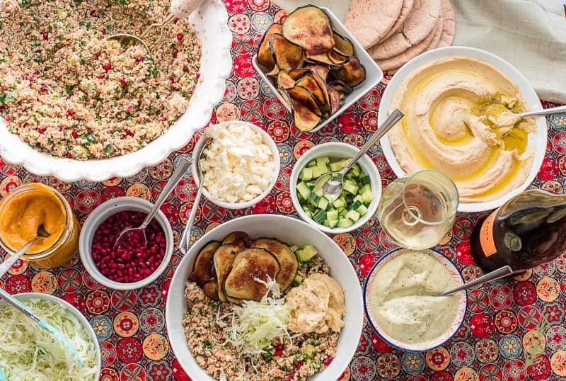 Shredded cabbage is added to the bowl with the tabbouleh, hummus, eggplant, and cucumber