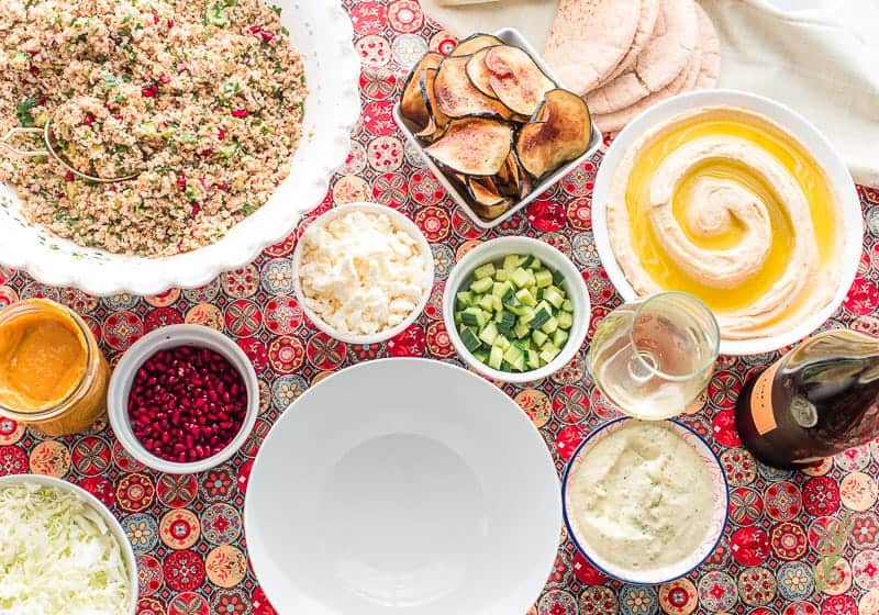 An empty white bowl surrounded by tabbouleh, eggplant chips, hummus, cucumber, wine, tahini sauce, feta cheese, pomegranate arils, amba sauce, and cabbage on a multi-colored towel