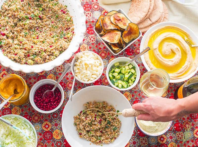 A hand begins the assembly of the Sabich Bowls by scooping tabbouleh into a large white bowl
